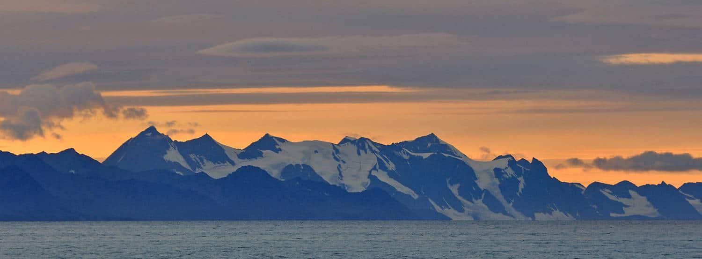 Die Gebirgskette der langen Insel Prins Karls Forland in abendlicher Beleuchtung.