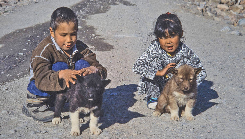 inuit-kinder-mit-jungen-schlittenhunden